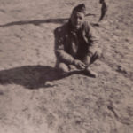 captain kneeling in sand